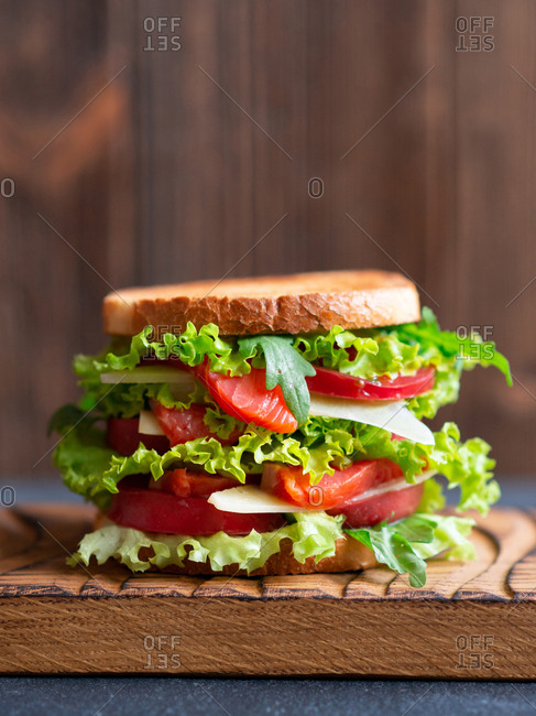 Sandwich with tomato, salmon, lettuce leaf, arugula and cheese