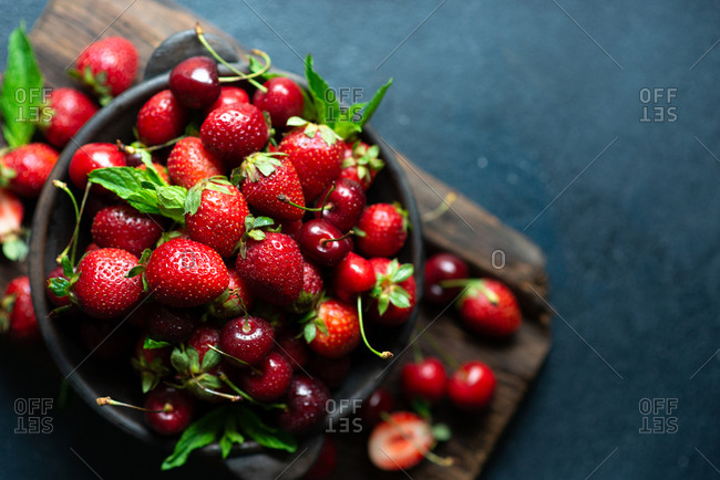Summer fruits and berries, top down view of cherries and strawberries in ceramic bowl