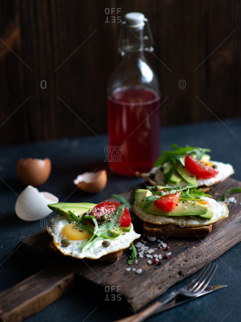 Avocado toasts with soft fried eggs, arugula and tomatoes on wooden cutting board on dark background