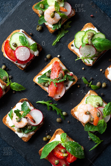 Sandwiches with soft cream cheese, shrimp, strawberry salmon and cucumber on dark background
