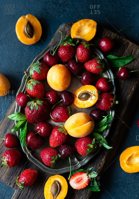Top down view of apricots, strawberries and cherries piled onto tray on dark background
