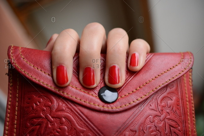 Close-up of a person with red nail polish holding leather clutch