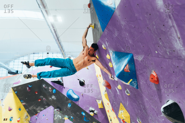 Young man climbing rock wall indoor