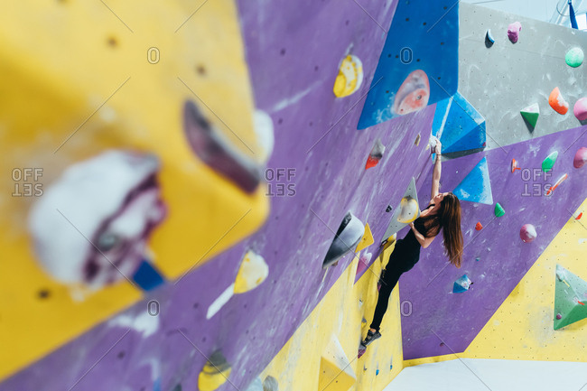 Young woman climbing rock wall indoor