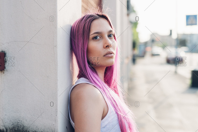 Portrait, young woman outdoor pink hair posing and looking at camera