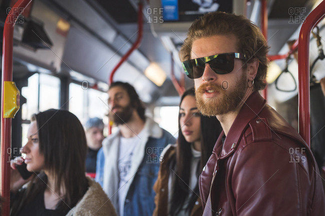 Young beautiful bearded man travelling on public transport