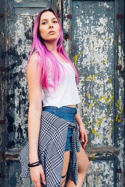 Young woman outdoor pink hair posing and looking at camera