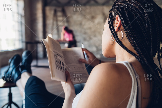 Back view young multiethnic woman sitting indoor reading book