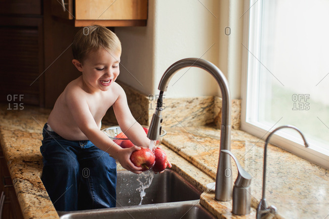 Toddler washing apples in the kitchen sink