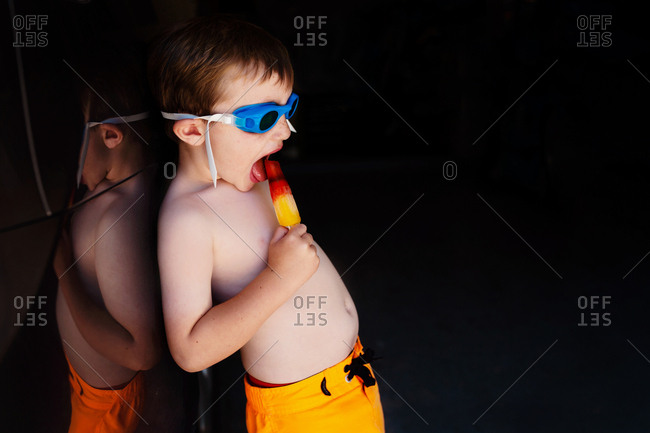 Toddler eating a popsicle in swim goggles