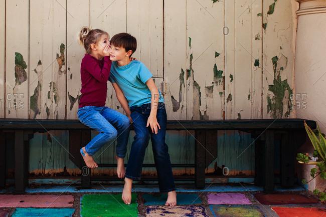 Kids telling secrets in a bright, colorful corner