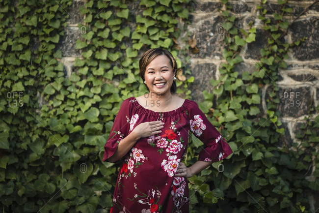 Portrait of Asian woman in front of ivy