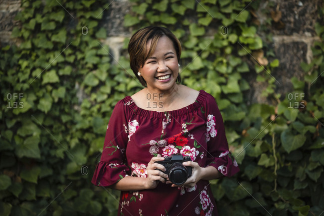 Portrait of Asian woman holding camera