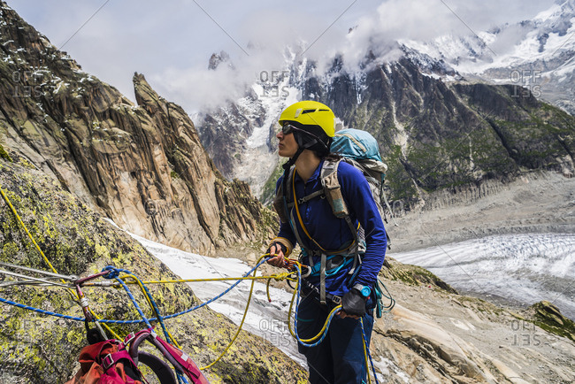 Female rock climber belaying partner, French Alps, Mer de Glace, Haute-Savoie, France