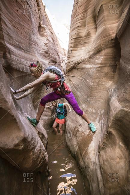 Two women canyoneering through narrow Zebra Canyon, Grand Staircase-Escalante National Monument, Utah, USA