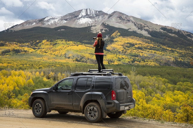 Woman photographing autumn scenery with mountain from top of 4x4 car, Crested Butte, Colorado, USA