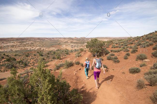 Two women hiking through desert at Grand Staircase-Escalante National Monument, Utah, USA