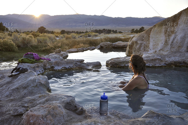 Woman soaking in hot spring at sunset