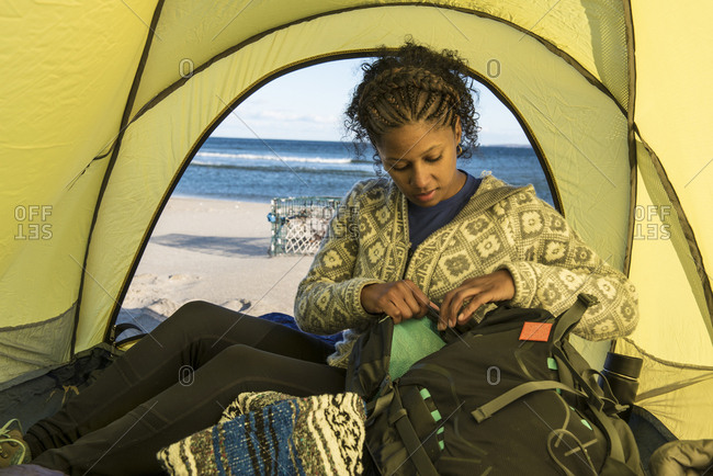 Woman camping on coastal beach, Newburyport, Massachusetts, USA
