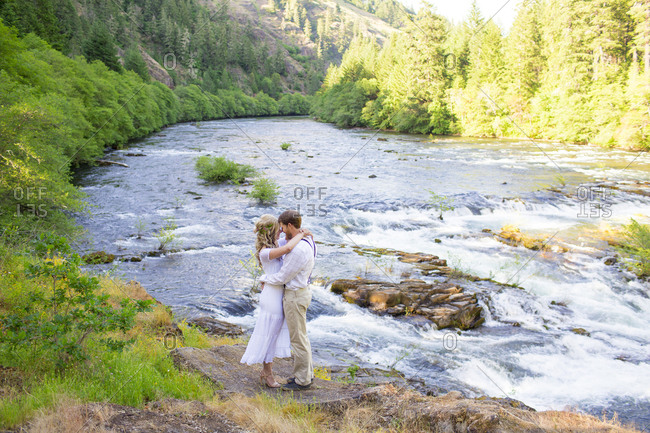 Bridge and groom embracing on riverbank, North Umpqua River, Glide, Oregon, USA