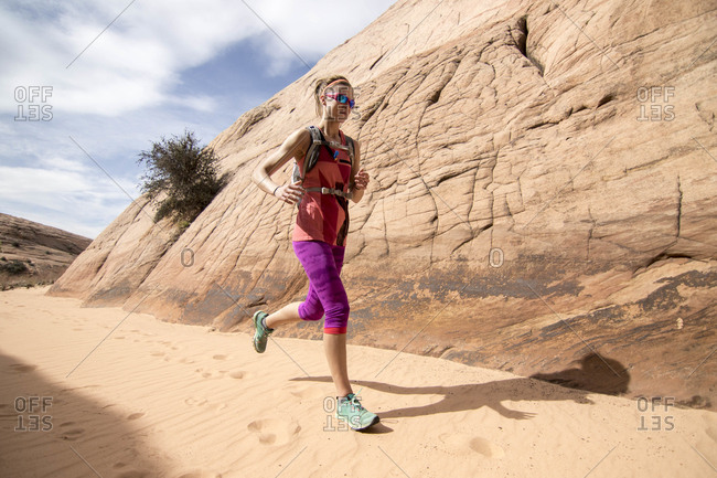 Woman trail running through Grand Staircase-Escalante National Monument, Utah, USA