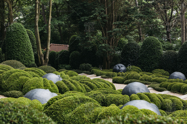 Etretat, Normandy, France - May 30, 2018: Round face sculptures in a garden in Les Jardins D'Etretat