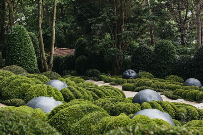 Etretat, Normandy, France - May 30, 2018: Round face sculptures in a garden in Les Jardins D'Etretat