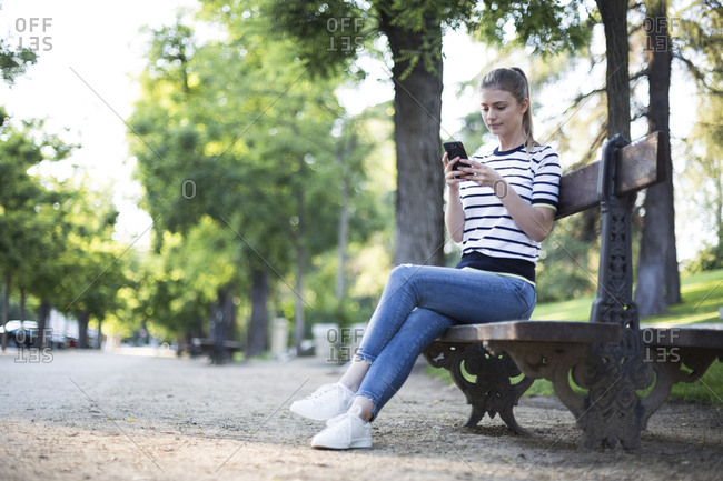 Beautiful woman sitting on a bench using her phone in Madrid, Spain