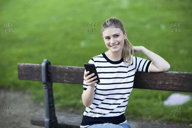 Beautiful woman smiling sitting on a bench using her phone and looking away