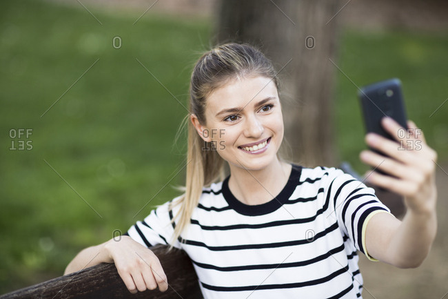 Beautiful woman smiling taking a selfie with her phone sitting on a bench