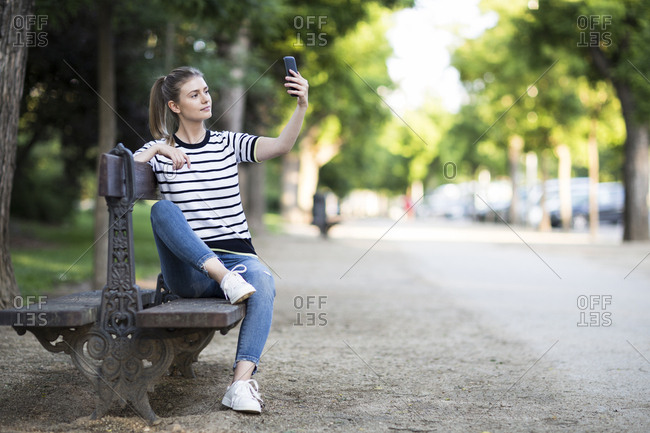 Woman taking a selfie with her phone sitting on a bench in Madrid, Spain