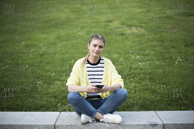 Beautiful woman with her phone sitting in a park in Madrid, Spain