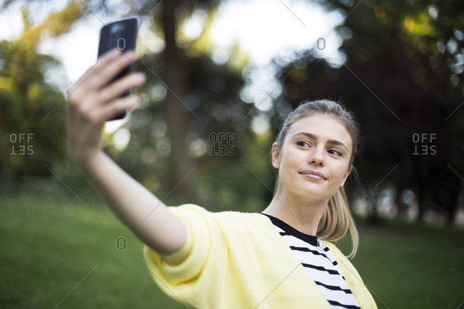 Beautiful woman taking a selfie with her phone in a park