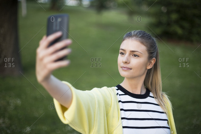 Young woman taking a selfie with her phone in a park in Madrid, Spain
