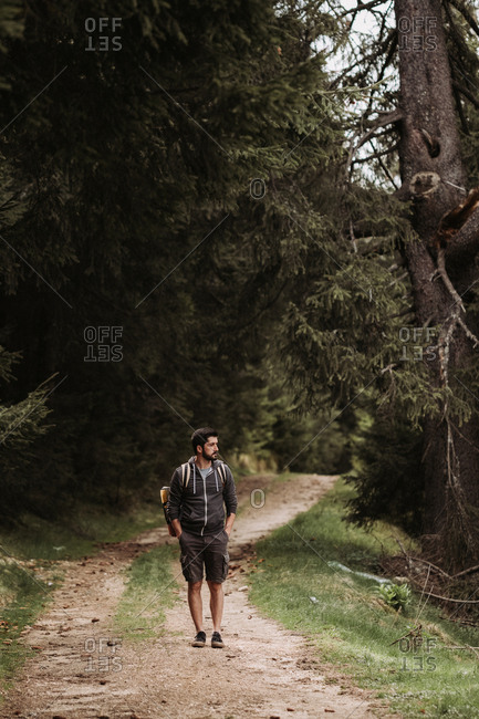 Man hiking on dirt road through forest