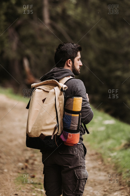 Man wearing backpack hiking in forest