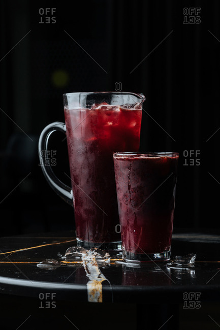 Cocktail in a pitcher and served in a glass on dark table
