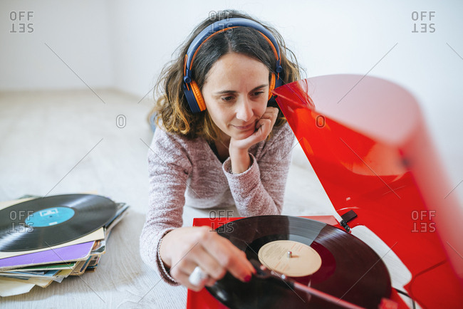 Young woman listening to vinyl on record player with headphones on