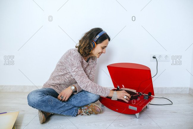 Young woman wearing headphones listening to record player in bare room