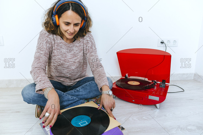 Woman looking at pile of vinyl records as she listens to retro looking record player
