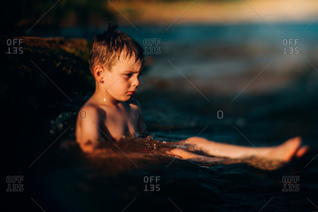 Unhappy young boy sitting in water bathed in afternoon light