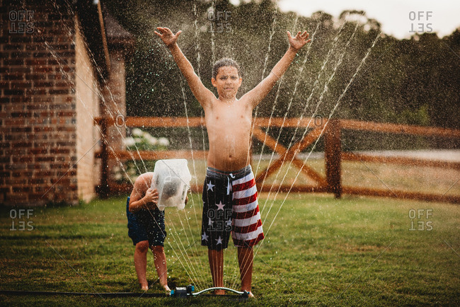 Young boy standing getting sprayed by garden sprinkler as brother covers face with plastic box