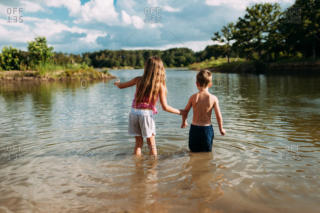 Rearview of young girl holding onto little brother as they wade into lake