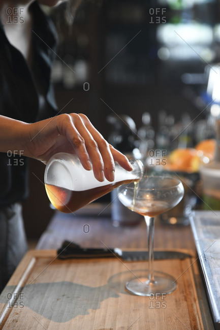 Bartender's hand pouring drink ingredients into stemmed glass