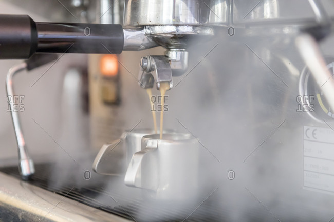 Espresso is poured from espresso machine, close up, in the unpackaged Stuckgut shop, Altona, Hamburg, Germany