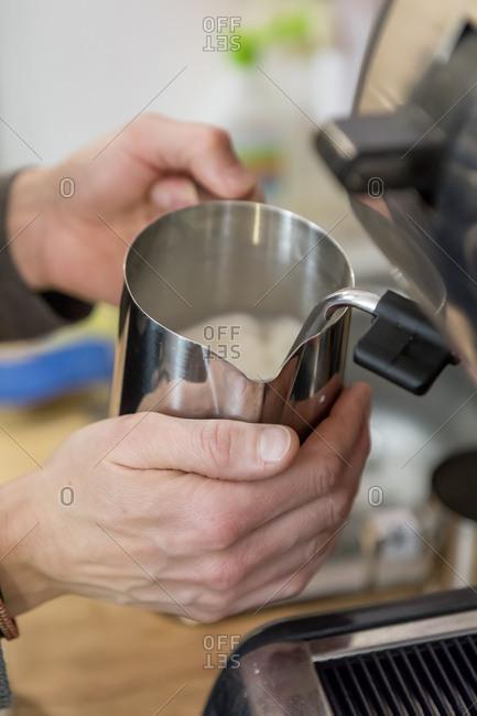 November 25, 2017: Frothing milk for Latte Macchiato, close up, in the unpackaged Stuckgut shop, Altona, Hamburg, Germany