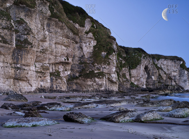 Northern Ireland, Antrim, Causeway Coast, steep coast made of mussel limestone close Ballintoy, blue hour, evening sky with moon