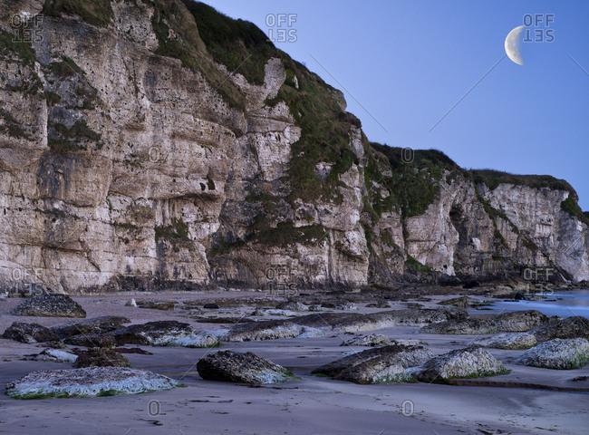 Northern Ireland, Antrim, Causeway Coast, steep coast made of mussel limestone close Ballintoy, blue hour, evening sky with moon