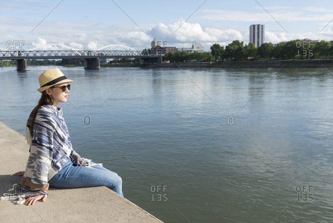 Young woman sits in the harbor promenade of Mannheim, Baden-Wurttemberg, Germany