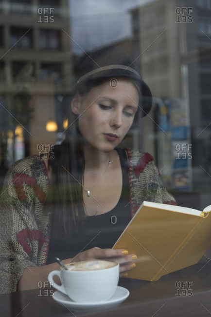 Young woman behind window in the cafe, semi-portrait